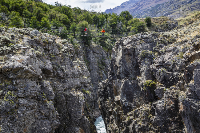 Patagonia, Aysen Region, Chile - February 14, 2016: Hikers crossing a Suspension bridge, Chacabuco Valley, Parque Patagonia
