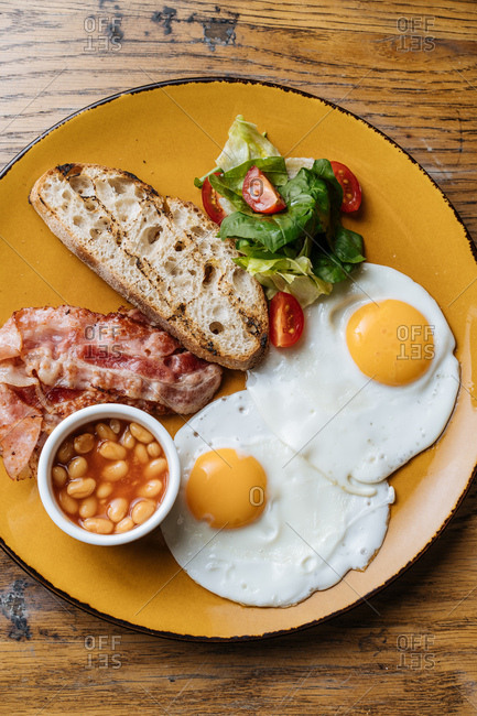 Top view of breakfast dish with eggs and bacon