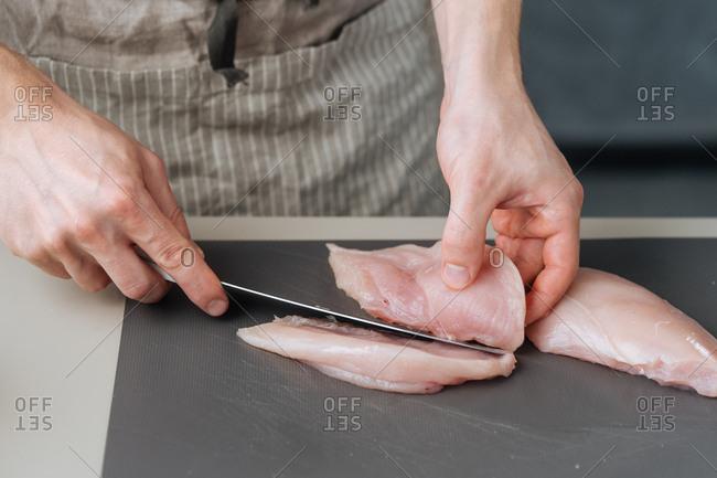 Man cutting chicken breasts