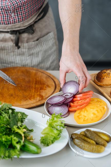 Man cutting veggies for burgers