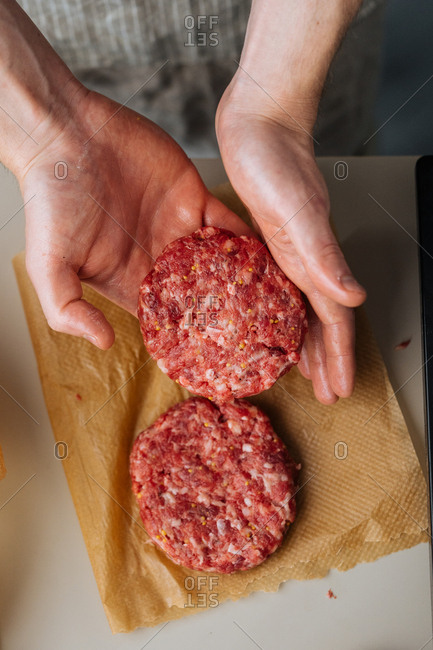 Overhead view of chef shaping meat for hamburgers