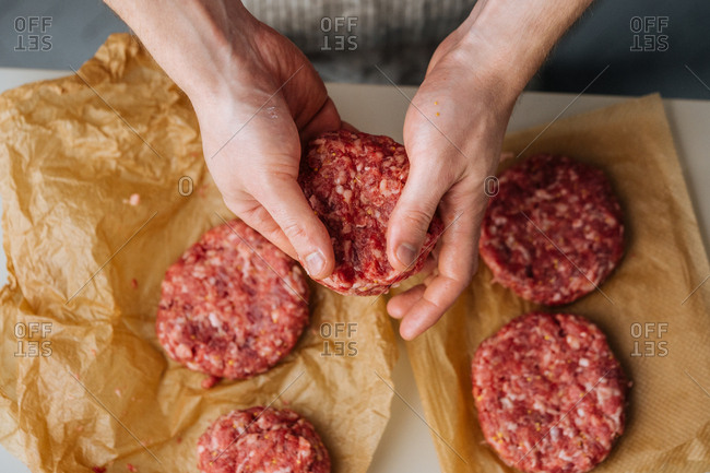Overhead view of man shaping meat for hamburgers