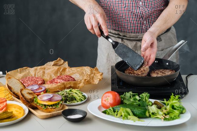 Man flipping hamburger patties in a pan