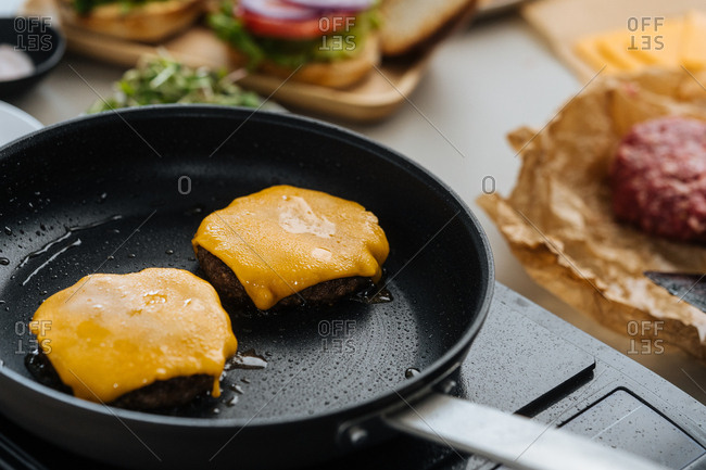 Hamburger patties with cheese cooking in a pan