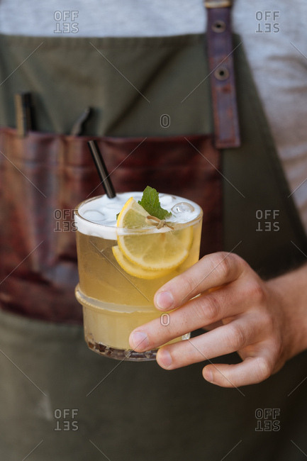 Man holding a yellow cocktail garnished with lemon slices