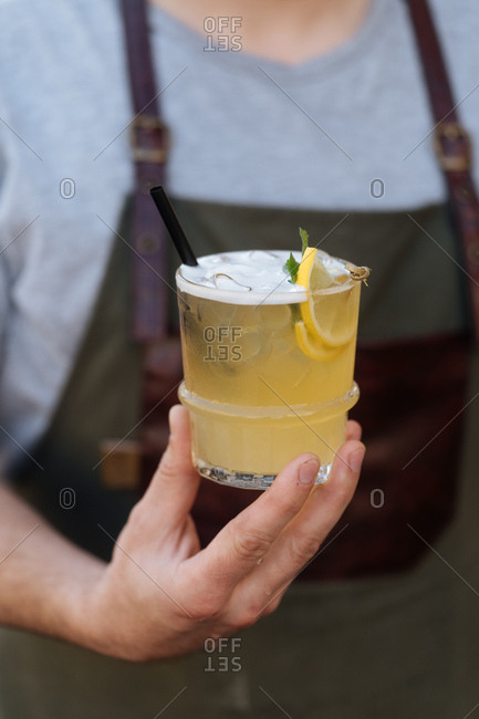 Man in an apron holding a yellow cocktail garnished with lemon slices