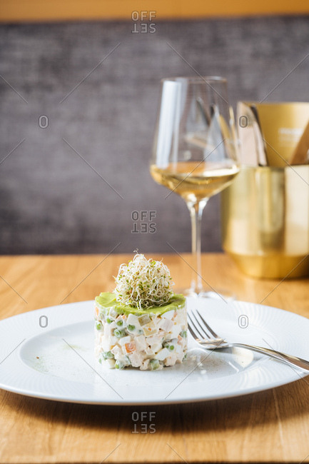 Imitation crab salad with peas with avocado and alfalfa sprouts on top