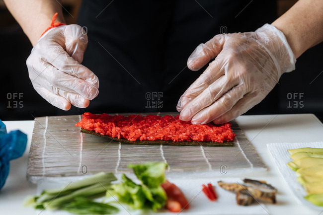 Close up of chef preparing sushi with red rice