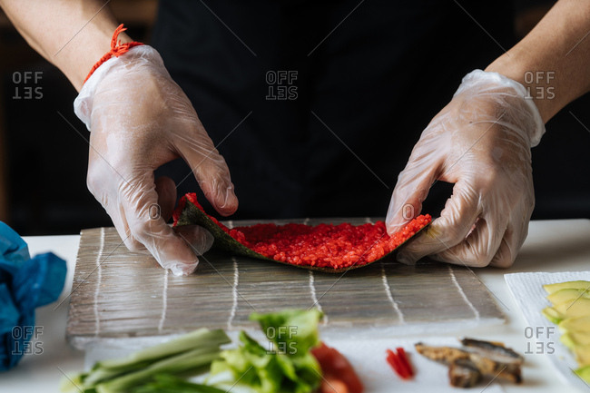 Close up of chef making sushi with red rice