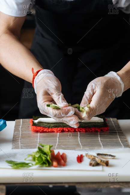 Close up of chef making sushi with red rice, cucumbers and cream cheese