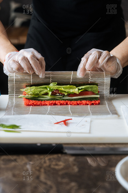 Close up of chef making vegetarian sushi with red rice