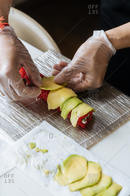 Close up of chef making vegetarian sushi with red rice and avocados on top