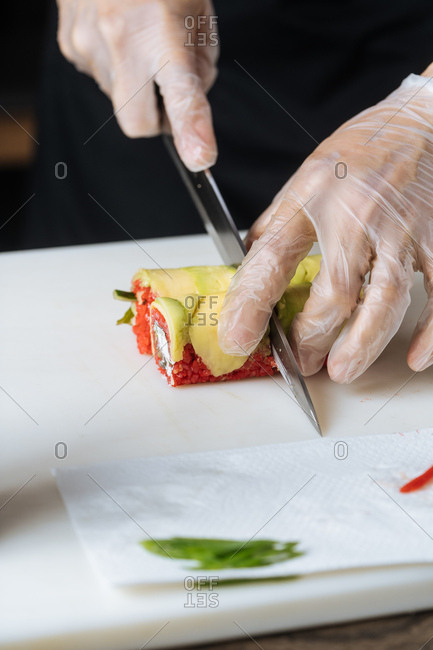 Close up of sushi chef slicing vegetarian sushi into rolls
