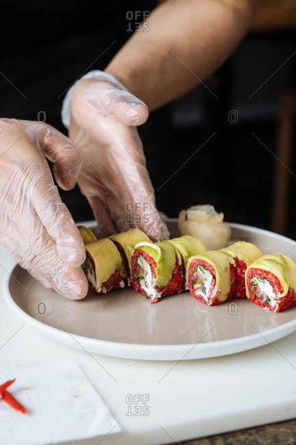 Close up of sushi chef plating vegetarian sushi with red rice and avocados