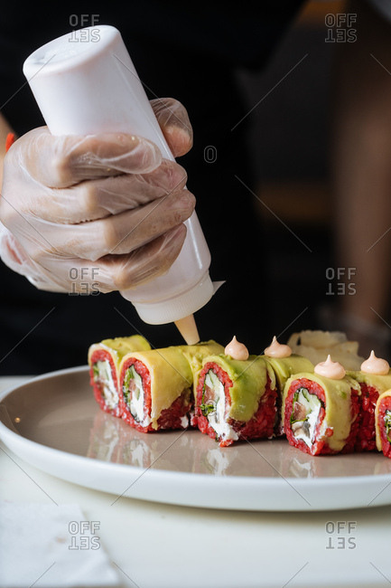 Close up of vegetarian sushi being garnished with small dollop of spicy mayo