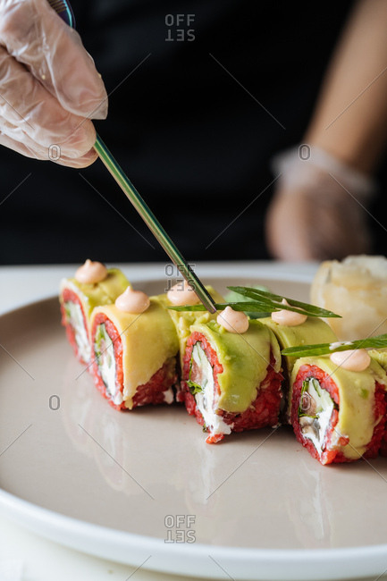 Close up of vegetarian sushi being garnished with small piece of greens