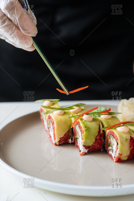 Close up of vegetarian sushi being garnished with small piece of pepper