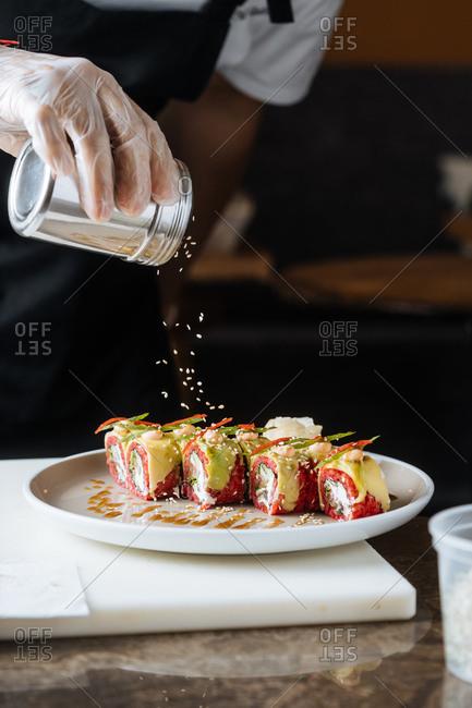 Close up of vegetarian sushi being garnished with sesame seeds