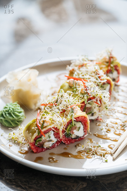 Sushi with beet-infused rice, cream cheese, tomato topped with alfalfa sprouts and avocado