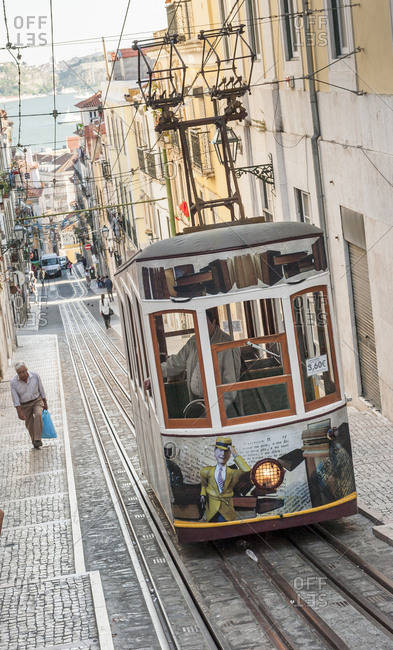 May 31, 2014: Old man walking along the Bica Funicular (Ascendor da Bica) in service since 1926 in  Lisbon, Portugal.