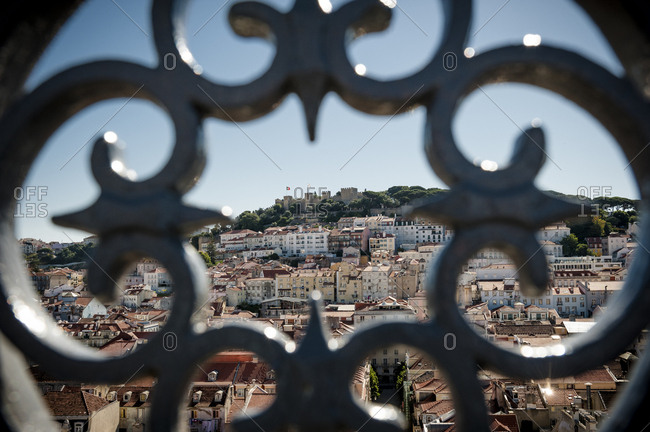 Castle Sao Jorge seen through a steel decorative detail of the Santa Justa Elevador in the center of Lisbon, Portugal.
