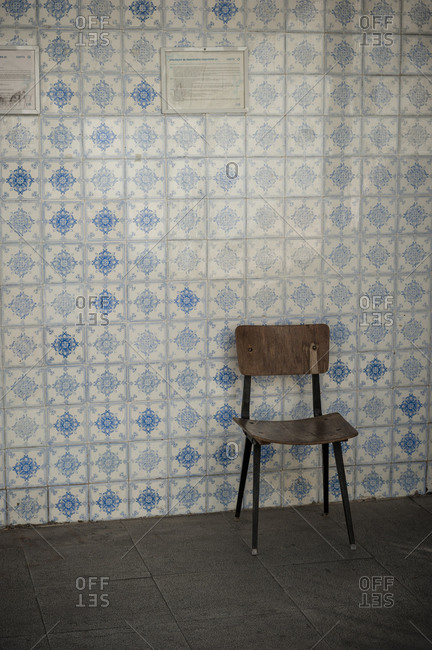 June 1, 2014: Chair in front of a tiled wall in a house in the city center of Lisbon.