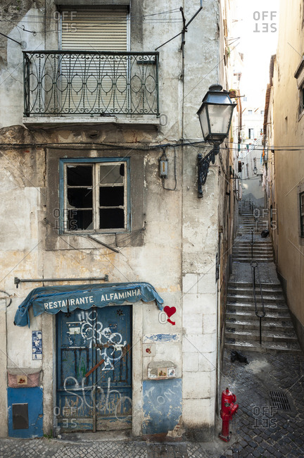 June 2, 2014: Abandoned shop with beautiful tiles next to a small staircase in the old Alfama district in Lisbon, Portugal.