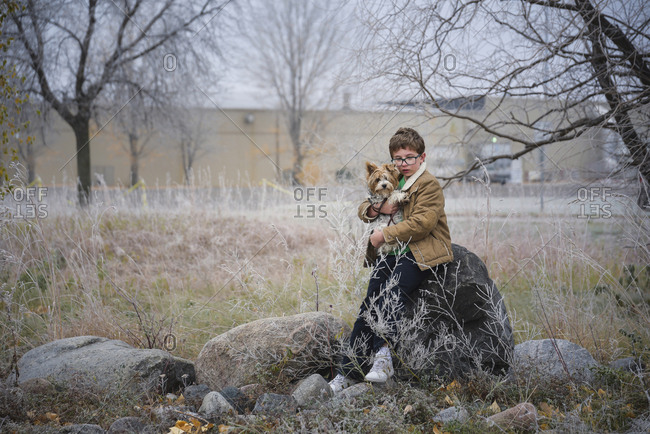 Boy carrying dog while leaning on rock amidst plants at park during winter