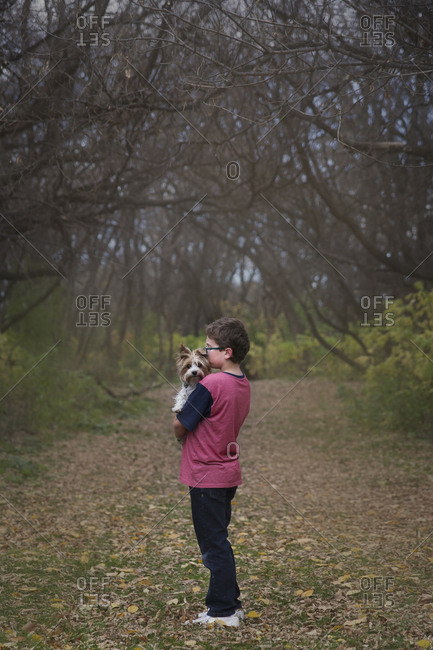 Boy carrying dog while standing on grassy field at park