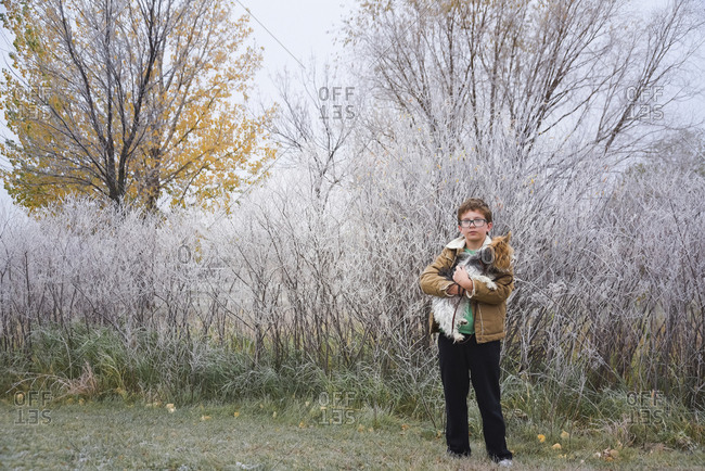 Portrait of boy carrying dog while standing on grassy field at park during winter