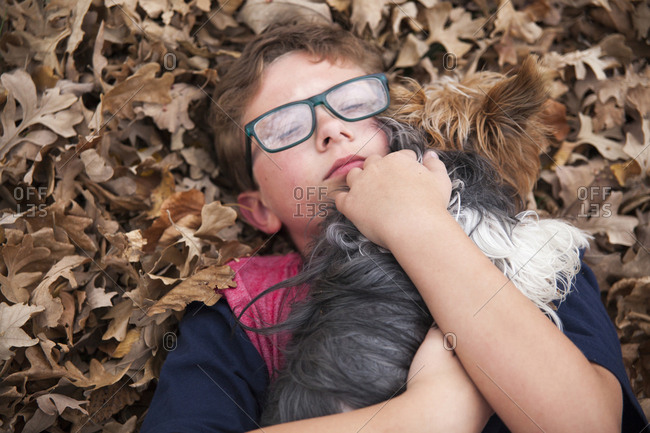 High angle view of boy embracing dog while lying on autumn leaves at park