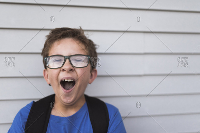 Close-up portrait of boy yawning while standing by wall