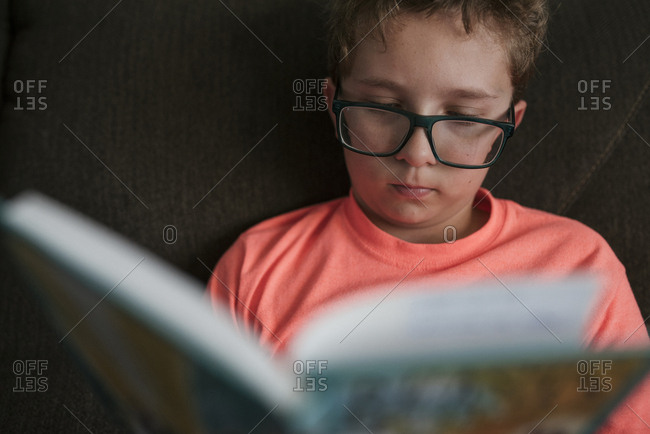 Close-up of boy studying while sitting on sofa at home