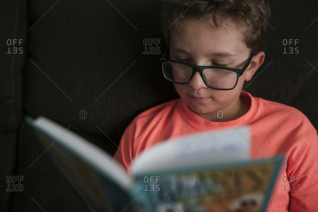 Close-up of boy wearing eyeglasses while studying on sofa at home