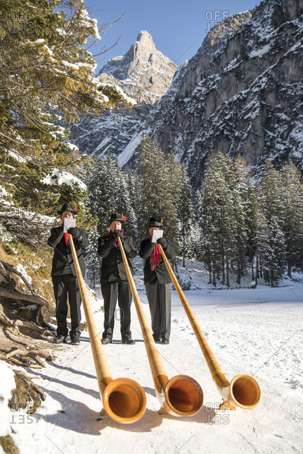 December 3, 2017: Musicians blowing alphorn on the shore of Braies lake during the Christmas markets of Braies, Pusteria valley, Trentino Alto Adige, Italy, Europe