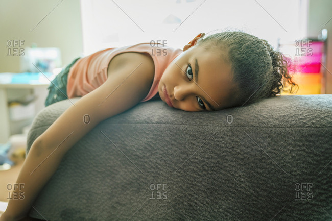Bored mixed-race girl pouting on couch