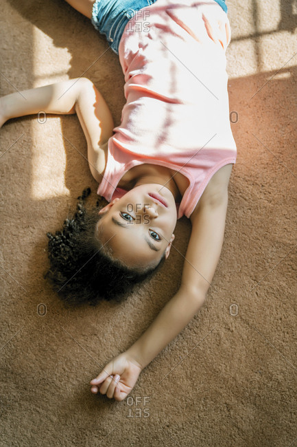 Girl laying on living room carpet in the sunlight