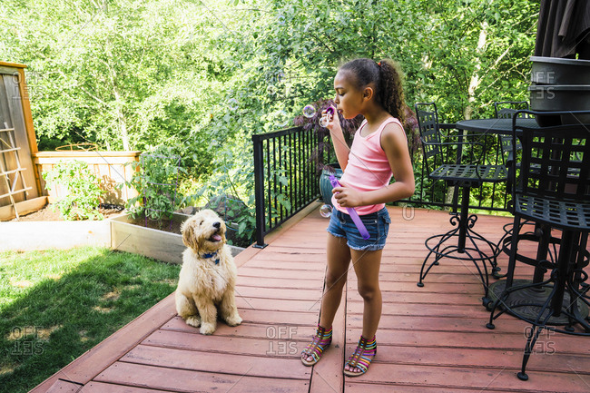 Tween Girl Blowing Bubbles with Labradoodle Puppy in Backyard
