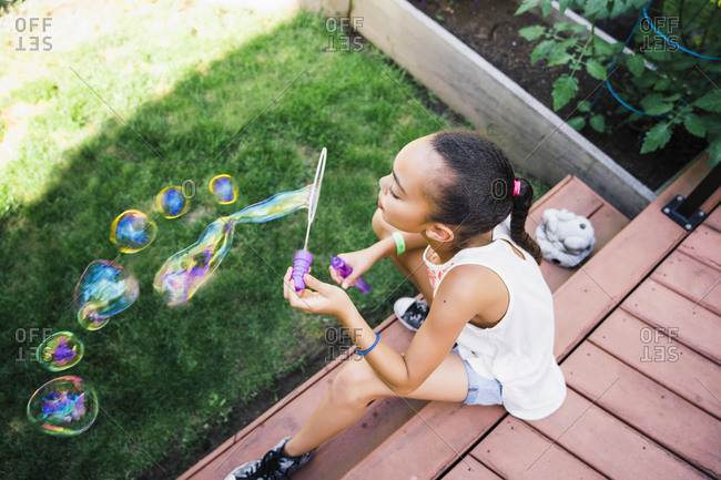 Tween Girl Blowing Bubbles in the Backyard