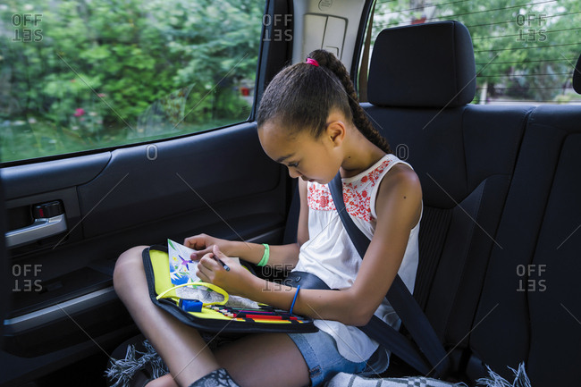 Girl drawing with colored pencils in back seat of car