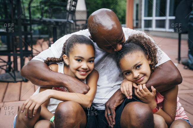 Portrait of happy dad hugging daughters in front of house