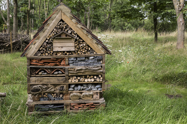 Large bug house with several layers of different materials in a garden.