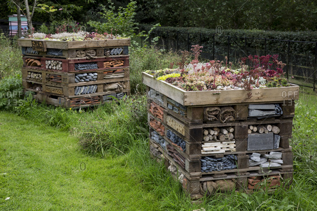 Two large bug houses with several layers of different materials in a garden.