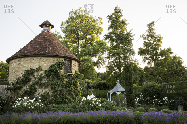 View of small round stone tower and pavilion from across a walled garden with trees and flowerbeds.