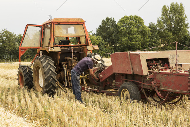 Tractor and straw baler in wheat field, farmer baling straw.