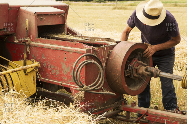 Tractor and straw baler in wheat field, farmer checking equipment.