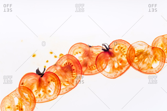 Tomato slices, juice and seeds backlit on white background