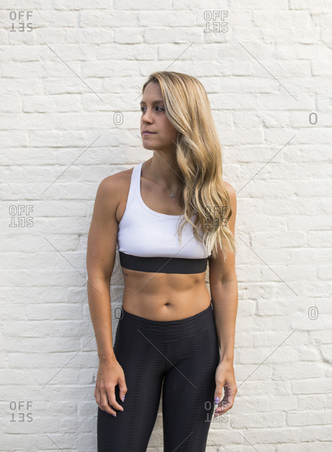 Young Adult Woman in Fitness Attire against White Brick Wall Looking Away