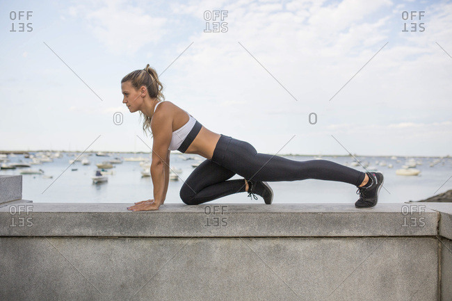 Young Adult Woman in Fitness Attire Exercising on Stone Wall