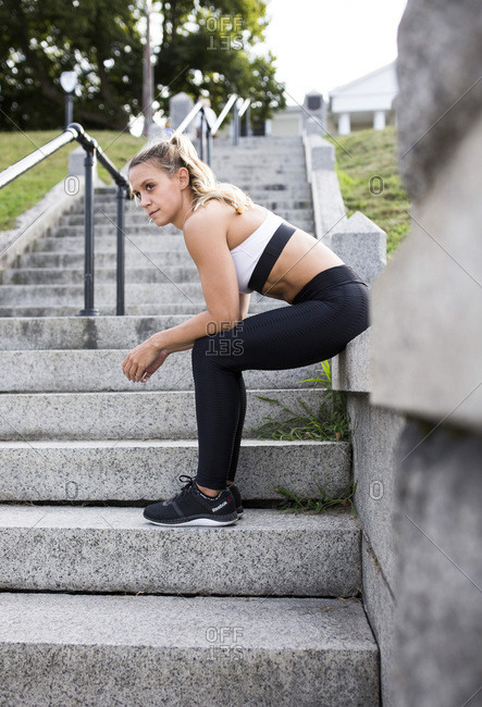Young Adult Woman in Fitness Attire Sitting on Stone Stairway Looking Away